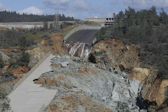 FILE - In this Feb. 28, 2017, file photo, a small flow of water drops down Oroville Dam's crippled spillway in Oroville, Calif. California plans to shut the shattered main spillway of the Oroville Dam for the summer on Friday, May 19 launching an all-out race to get it operational again before the next rainy season.  (AP Photo/Rich Pedroncelli, File)