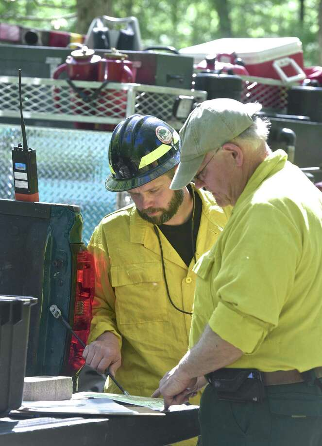 Jim Villwock, Connecticut DEEP, left, and Larry Rousseau, Connecticut Division of Forestry, check a map before heading out to a brush fire in Kent on Thursday morning. May 18, 2017, in Kent, Conn. Photo: H John Voorhees III / Hearst Connecticut Media / The News-Times