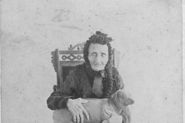 In this undated photo, Madam Candelaria poses with her dog. The woman, who claimed to have been nursing the ailing Jim Bowie when he was killed by Santa Anna's army at the Battle of the Alamo, lived to be 113. She said her dog slept on her feet and kept her rheumatism at bay.