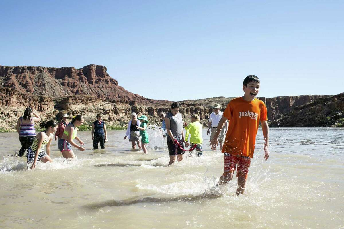 Grandparents and grandchildren swim the Colorado River during an educational trip organized by Road Scholar.