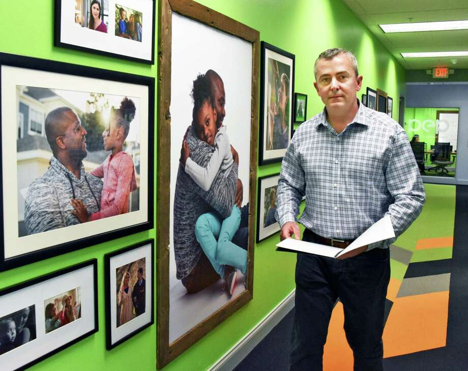 President and founder of Patient Experience Project Dan Bobear walks through a corridor decorated with photographs of patients and care givers Wednesday May 17, 2017 in Saratoga Springs, NY.  (John Carl D'Annibale / Times Union) Photo: John Carl D'Annibale / 20040473A