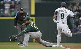 Oakland Athletics first baseman Yonder Alonso drops the ball as Seattle Mariners' Boog Powell (8) arrives at first base with a single during the second inning of a baseball game Wednesday, May 17, 2017, in Seattle. (AP Photo/Elaine Thompson)