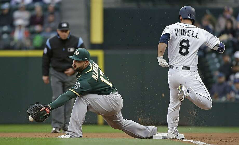 Oakland Athletics first baseman Yonder Alonso drops the ball as Seattle Mariners' Boog Powell (8) arrives at first base with a single during the second inning of a baseball game Wednesday, May 17, 2017, in Seattle. (AP Photo/Elaine Thompson) Photo: Elaine Thompson, Associated Press