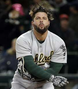 Oakland Athletics' Yonder Alonso pulls off his batting gear after striking out swinging to end the top of the first inning of a baseball game against the Seattle Mariners, Monday, May 15, 2017, in Seattle. (AP Photo/Elaine Thompson)