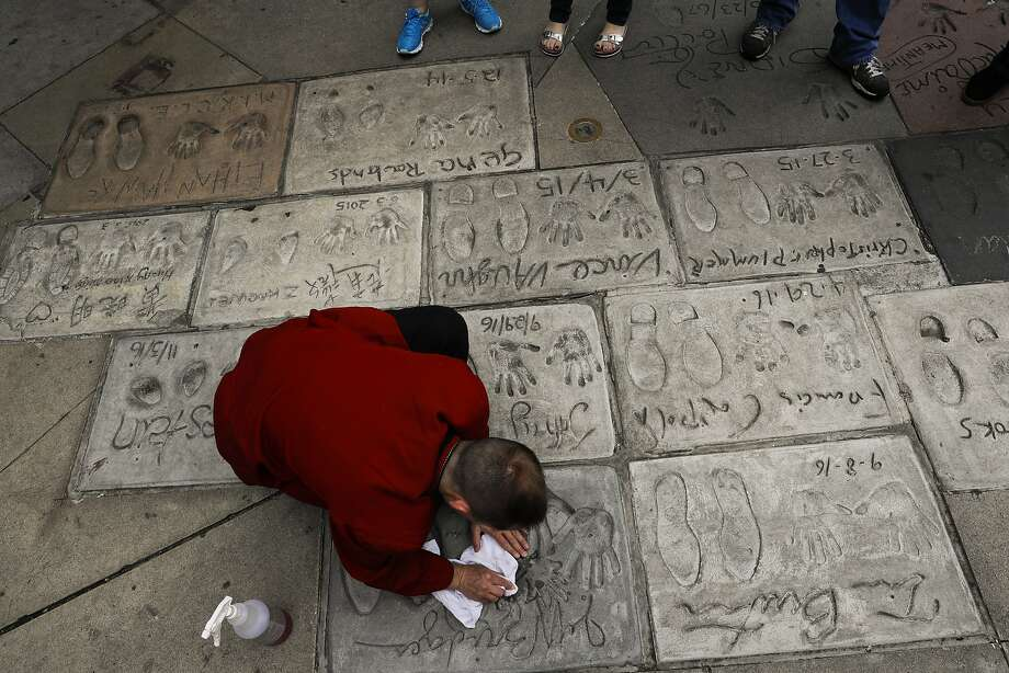 In this May 9, 2017 photo, door staff Chris Bayus cleans the hand and footprints of Hollywood stars in the forecourt of the TCL Chinese Theatre in Los Angeles. The storied Hollywood Boulevard movie palace, originally named Grauman's Chinese Theatre, opened its doors on May 18, 1927. (AP Photo/Jae C. Hong) Photo: Jae C. Hong, Associated Press