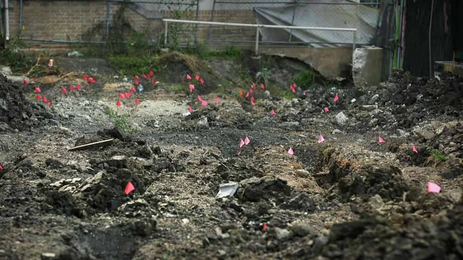 Red flags mark the location where bone fragments have been found at the excavation site. Photo: Bob Owen / San Antonio Express-News / ©2017 San Antonio Express-News