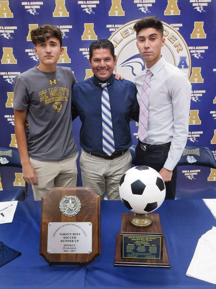 Alexander soccer head coach Danny Hermosillo, center, celebrated with Max De Leon, left, and Victor Ayala as the two signed their national letters of intent to continue their athletic carrers. De Leon signed with St. Mary's while Ayala inked with TAMIU. Photo: Cuate Santos /Laredo Morning Times / Laredo Morning Times