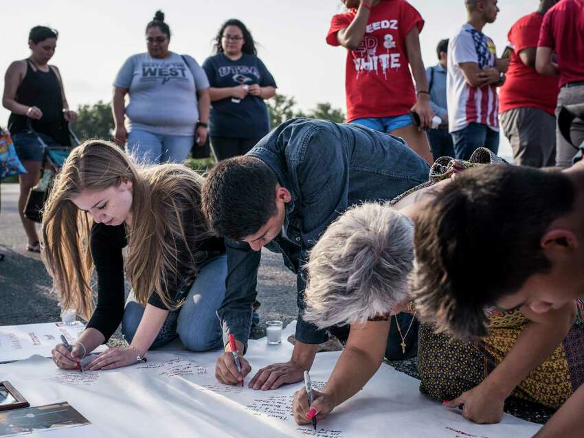 From left, student sophomore Katie Bulen, junior Jimmy Gomez, and mother of a student Elsa Zamora, all sign their thoughts on a poster during the vigil of Tommy Garcia, principal at Taft High School, who died at 56 years old after a short illness on Thursday, May 18, 2017.