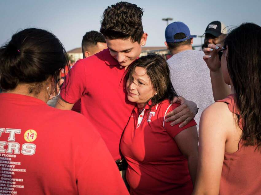 Vice Principal Martha Fernandez, center right, hugs senior Steven Sanchez, after saying a few words during the vigil of Tommy Garcia, principal at Taft High School, who died at 56 years old after a short illness on Thursday, May 18, 2017.
