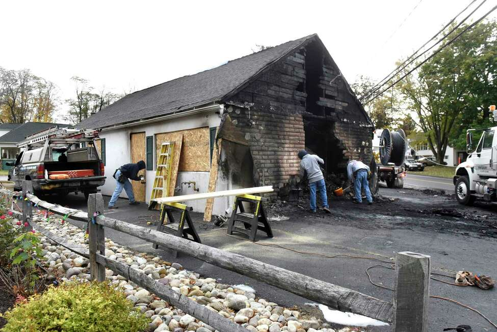 Brothers, who are friends with the tavern owner, work to board and clean up fire debris on Saturday, Oct. 29, 2016, at Blessing's Tavern in Colonie, N.Y. From left are Ken Klouse, Andrew Klouse and Anthony Klouse. (Cindy Schultz / Times Union)
