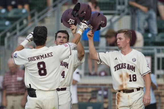 Texas A&M freshman second baseman Braden Shewmake (8) taps helmets with teammates Cam Blake (4) and Nick Choruby (18) to celebrate a three-run homer against Arkansas, Thursday, May 18, 2017, at Olsen Field in College Station, Texas.