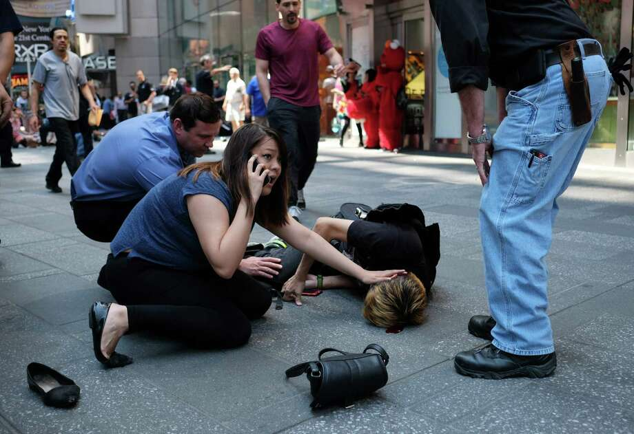 TOPSHOT - EDITORS NOTE: Graphic content / People attend to an injured man after a car plunged into him in Times Square in New York on May 18, 2017.  A car plowed into a crowd of pedestrians in New York's bustling Times Square, leaving one person dead and at least 12 other injured in what officials said was an accident.  / AFP PHOTO / Jewel SAMADJEWEL SAMAD/AFP/Getty Images ORG XMIT: Car strik Photo: JEWEL SAMAD / AFP or licensors