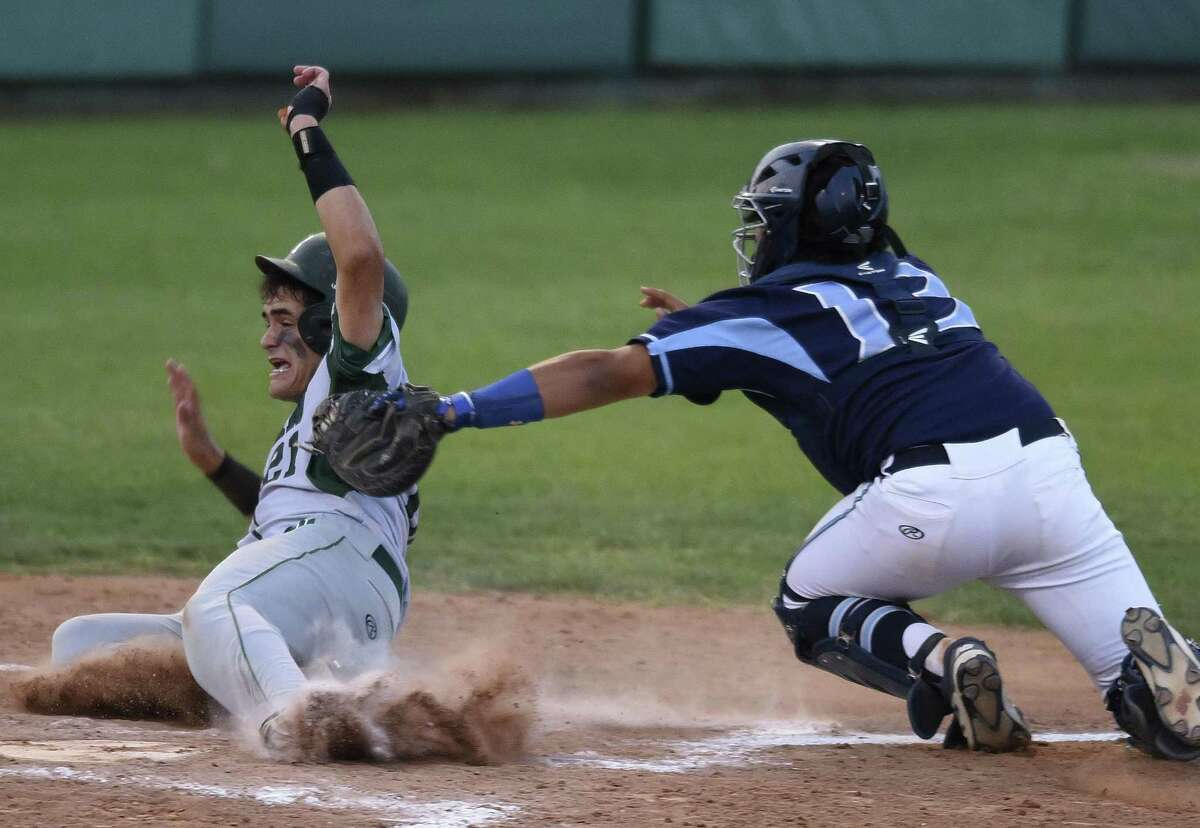 Ramon Garza of Reagan is tagged out by Johnson catcher Dominic Tamez during Game 1 of their Class 6A third-round playoff series on May 18, 2017.