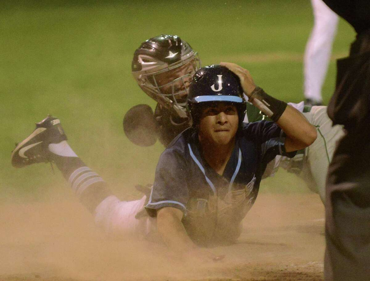 Dante Tamez of Johnson scores as Reagan catcher Mac Papini applies a tag during fifth-inning action of Game 1 of their Class 6A third-round series on Thursday, May 18, 2017.