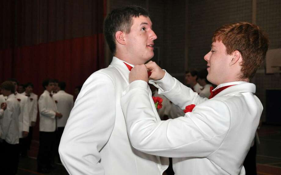 Dan O'Rourke, of Newtown helps classmate Quinn Rooney, of Stratford, with his bow tie in the staging area before the start of Fairfield College Preparatory School's 68th Commencement ceremony on Sunday, June 6, 2010. Photo: Amy Mortensen / Connecticut Post Freelance