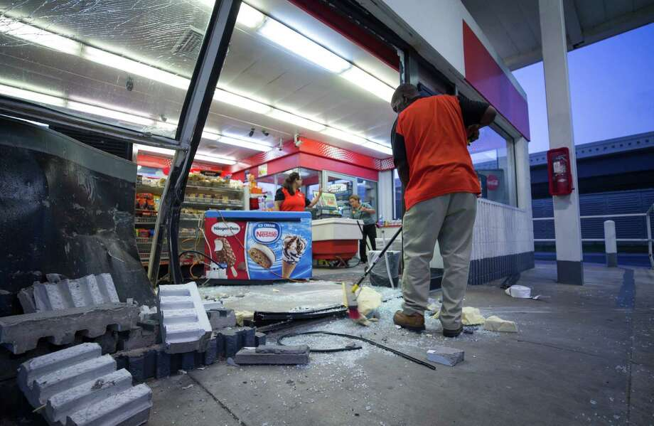 Shell gas station workers clean up the front entrance after a smash and grab at 2562 North Loop West Friday, May 19, 2017, in Houston. Photo: Godofredo A. Vasquez / Houston Chronicle