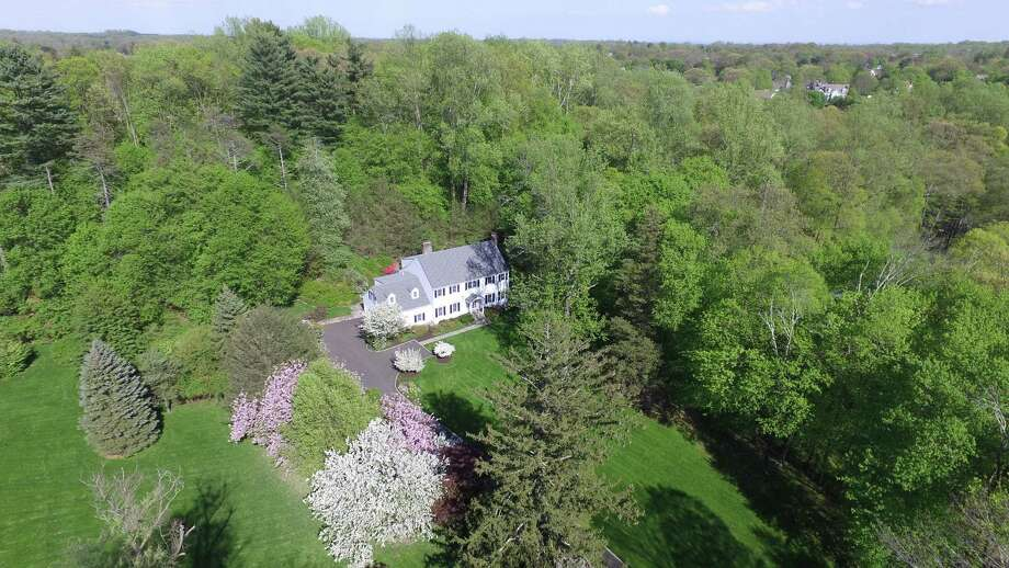 The colonial house at 222 Marshall Ridge Road sits on a 1.69-acre largely level and sloped property, which has many colorful azalea bushes, rhododendrons, and mature trees. Photo: /