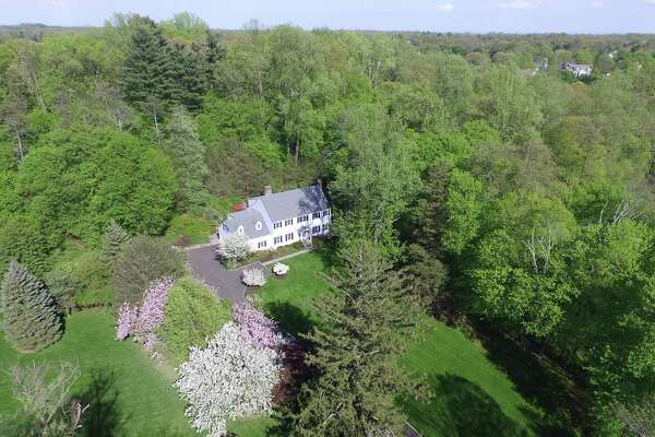 The colonial house at 222 Marshall Ridge Road sits on a 1.69-acre largely level and sloped property, which has many colorful azalea bushes, rhododendrons, and mature trees.