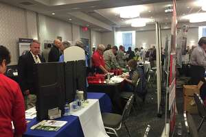 Active military and veterans confer with employers at this week's RecruitMilitary job fair at the Norris Conference Centers, attended by about 500 job seekers.