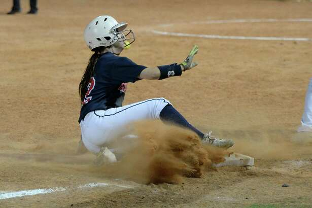 Lauren Bazan (12) of Atascocita slides into third base on a sacrifice fly hit by London Marder (21) in the seventh inning of an regional semifinal playoff softball game between the Katy Tigers and the Atascocita Eagles on Thursday May 18, 2017 at Katy HS, Katy, TX.