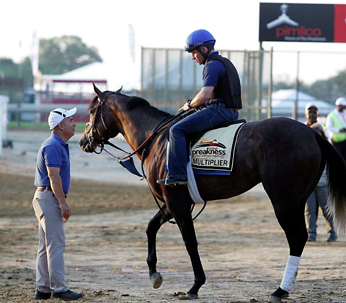 Trainer Mark Casse, left, talks with fellow conditioner Brendon Walsh, riding his Preakness Stakes entrant Multiplier, at Pimlico Race Course in Baltimore, Friday, May 19, 2017. Casse is the trainer of Classic Empire. (AP Photo/Garry Jones) ORG XMIT: MDGJ103