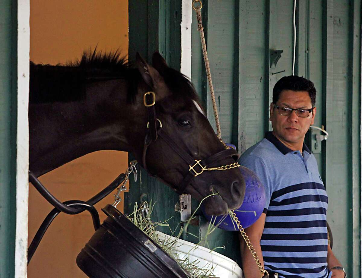 Juan Aguayo watches as Kentucky Derby winner Always Dreaming munches on his breakfast in Stall 40 of the stakes barn at Pimlico Race Course in Baltimore, Friday, May 19, 2017. (AP Photo/Garry Jones) ORG XMIT: MDGJ104