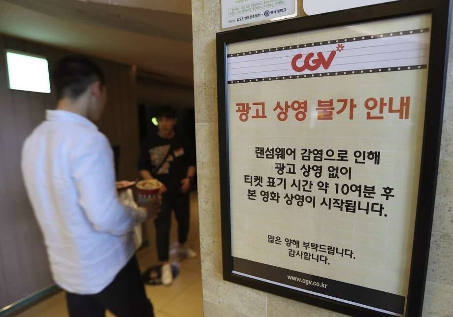 "A customer walks by the notice about ""ransomware"" at CGV theater in Seoul, South Korea, Monday, May 15, 2017. The letters read ""Due to ransomware affection, we are unable to screen advertisement. The movie is going to start 10 minutes after the ticket time."" (AP Photo/Lee Jin-man) Photo: Lee Jin-man, STF / Associated Press / Copyright 2017 The Associated Press. All rights reserved."