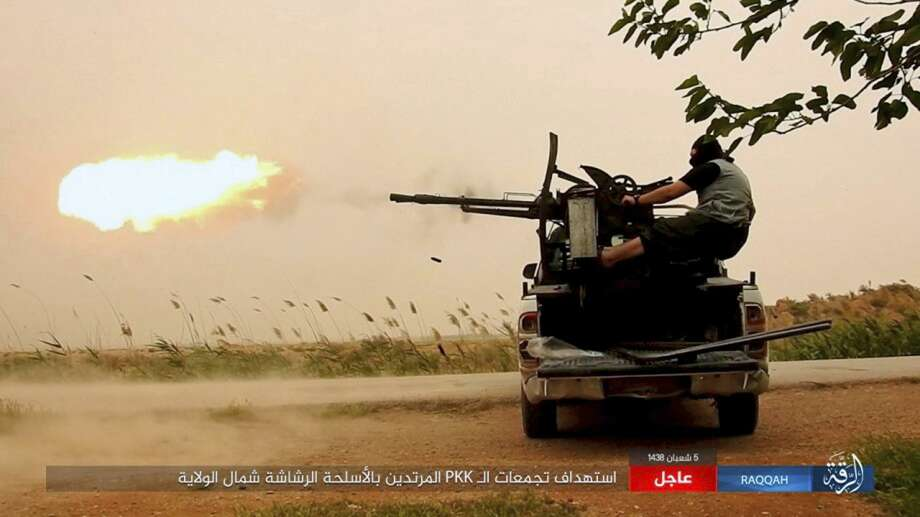 """FILE -- This undated image posted online Monday, May 1, 2017, by supporters of the Islamic State militant group on an anonymous photo sharing website, purports to show an Islamic State fighter firing his weapon during clashes with U.S.-backed Kurdish-led Syrian Democratic Forces, in the northern Syrian province of Raqqa. A top Syrian Kurdish official said Wednesday, May 10, 2017, that the U.S. decision to arm Kurdish fighters with heavier weapons will help legitimize the force, which is denounced as a terrorist organization by Turkey. The Trump administration announced Tuesday it will arm the Kurdish-led Syrian Democratic Forces """"as necessary"""" to recapture the Islamic State stronghold of Raqqa. (Militant Photo via AP) Photo: Uncredited, HONS / Associated Press / Militant Photo"""