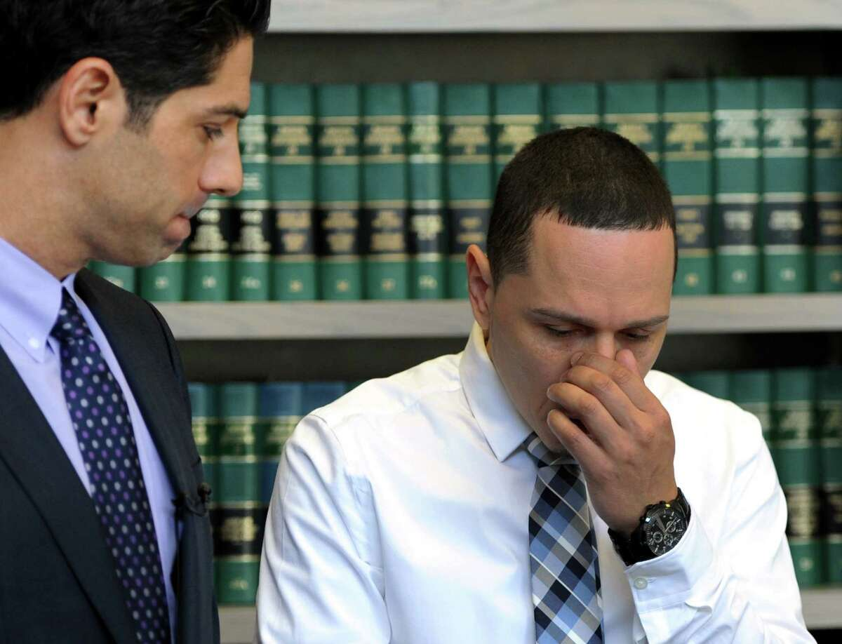Juan Negron, right, father of Jayson Negron, listens as his lawyer, Michael Rosnick makes a statement to the press in the law office on Broad Street in Bridgeport, Conn. on Friday, May 19, 2017.