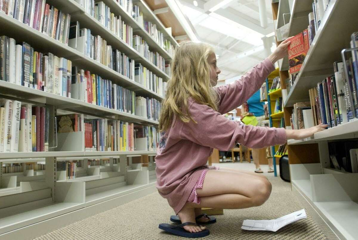 Stamford_062708_ Maddy Burns (age 13) searches the shelves of the Harry Bennett branch of the Ferguson library for books that are on her Summer reading st. Maddy will be a freshman at Stamford High School this coming school year and students are given a list of books to read over the Summer. The library will be cutting back on the hours that they will be open due to budget cuts. Mark Conrad/Staff photo Staff Photo Mark Conrad