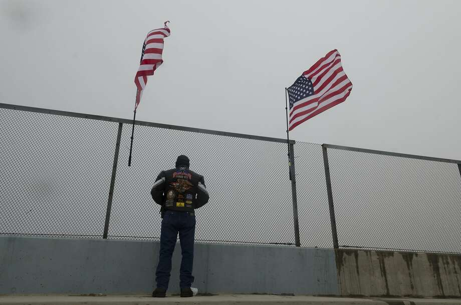 Ernie Kopasz watches traffic on the Interstate 15 from the Oak Hills Road bridge in Hesperia (San Bernardino County) on Wednesday. Kopasz hung American flags to welcome motorcyclists on the Rolling Thunder ride as they rode through the area on their way to the Vietnam Veterans Memorial in Washington, D.C. Photo: JAMES QUIGG, Associated Press
