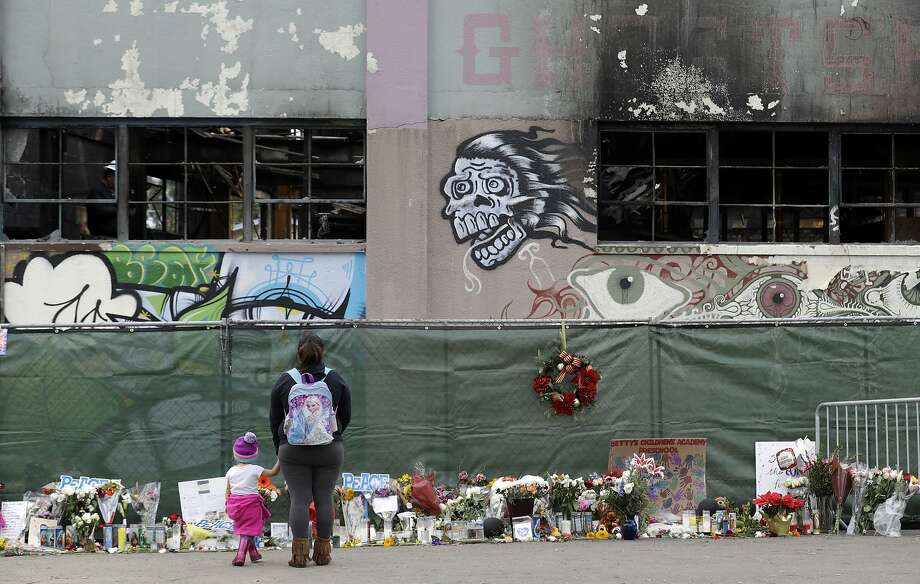 FILE - In this Dec. 13, 2016 file photo, flowers, pictures, signs and candles, are placed at the scene of a warehouse fire in Oakland, Calif. Attorneys representing the families of people who died in the Northern California warehouse fire that broke out during an unlicensed concert plan to file an updated lawsuit against the building's owner and manager Tuesday, May 16, 2017. (AP Photo/Marcio Jose Sanchez, File) Photo: Marcio Jose Sanchez, Associated Press