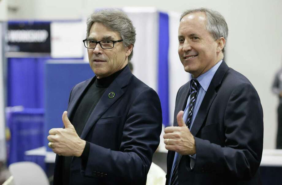 U.S. Secretary of Energy Rick Perry, left, an Texas Attorney General Ken Paxton pose for photos during a tour of Earth Day displays at Fair Park in Dallas, Friday, April 21, 2017. (AP Photo/LM Otero) Photo: LM Otero, STF / Associated Press / Copyright 2017 The Associated Press. All rights reserved.
