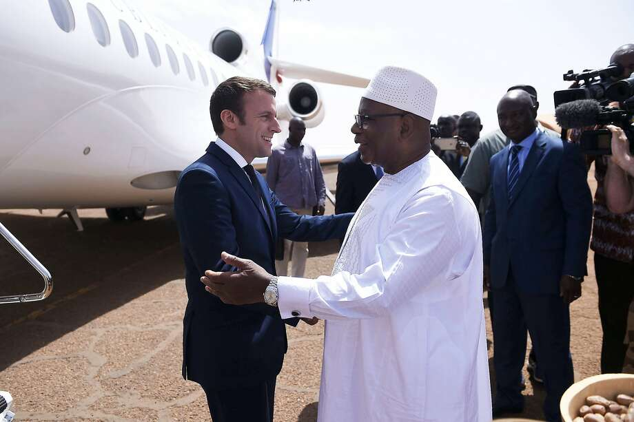 French President Emmanuel Macron, left, is greeted by Mali's President Ibrahim Boubacar Keita as he arrives to meet French soldiers of Operation Barkhane, France's largest overseas military operation, in Gao, Northern Mali, Friday, May 19, 2017. On his first official trip outside Europe, new French President Emmanuel Macron is highlighting his determination to crush extremism with a visit to French-led military forces combating jihadist groups in West Africa. (Christophe Petit Tesson, Pool via AP) Photo: Christophe Petit Tesson, Associated Press