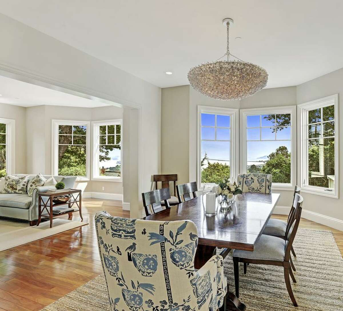 The dining area features contemporary lighting and a bay of windows.