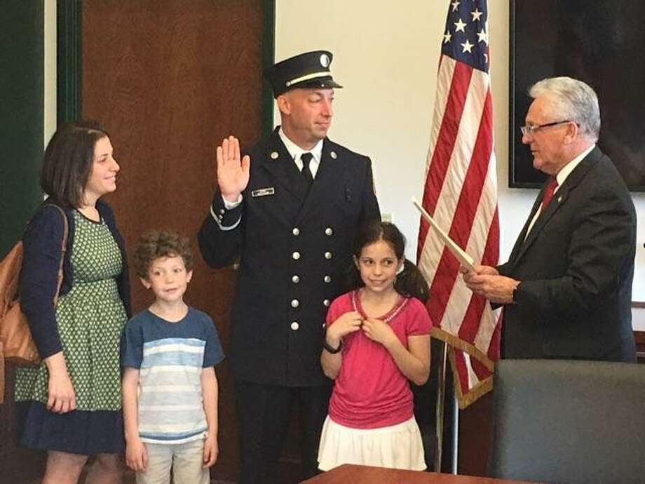 Following his March promotion from Norwalk firefighter to lieutenant, Adam Sussman was formally sworn in this week at a meeting of the Board of Fire Commissioners by Mayor Harry Rilling. His wife Stacey and children, Hannah and Milo, were in attendance to pin his lieutenant's badge on. Photo: Contributed Photo