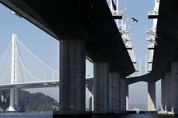 A cormorant flies between both viaducts of the new eastern Bay Bridge where nesting platforms are installed in Oakland, Calif. on Friday, May 19, 2017. Now that the old bridge has been dismantled, cormorants have finally taken up residence on the specially designed nesting platforms after years of coaxing from Caltrans and wildlife officials.