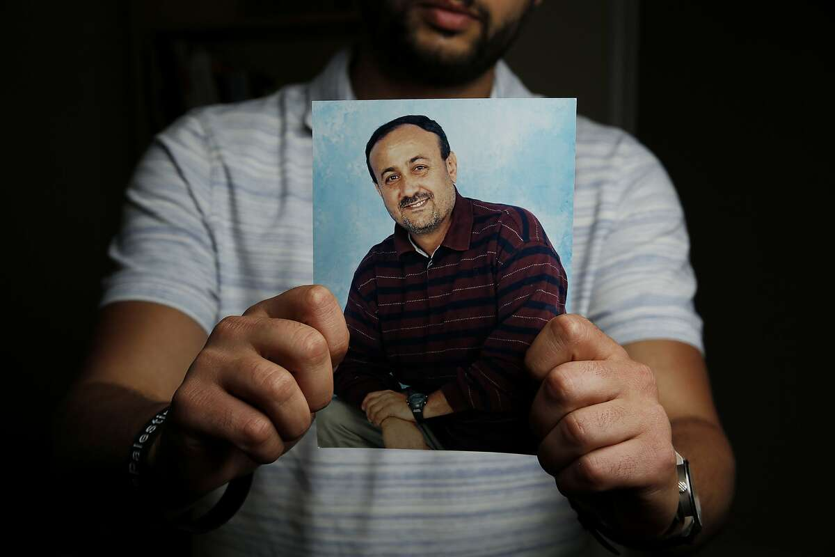 Arab Barghouti holds a photo of his father, Marwan Barghouti, in Belmont.