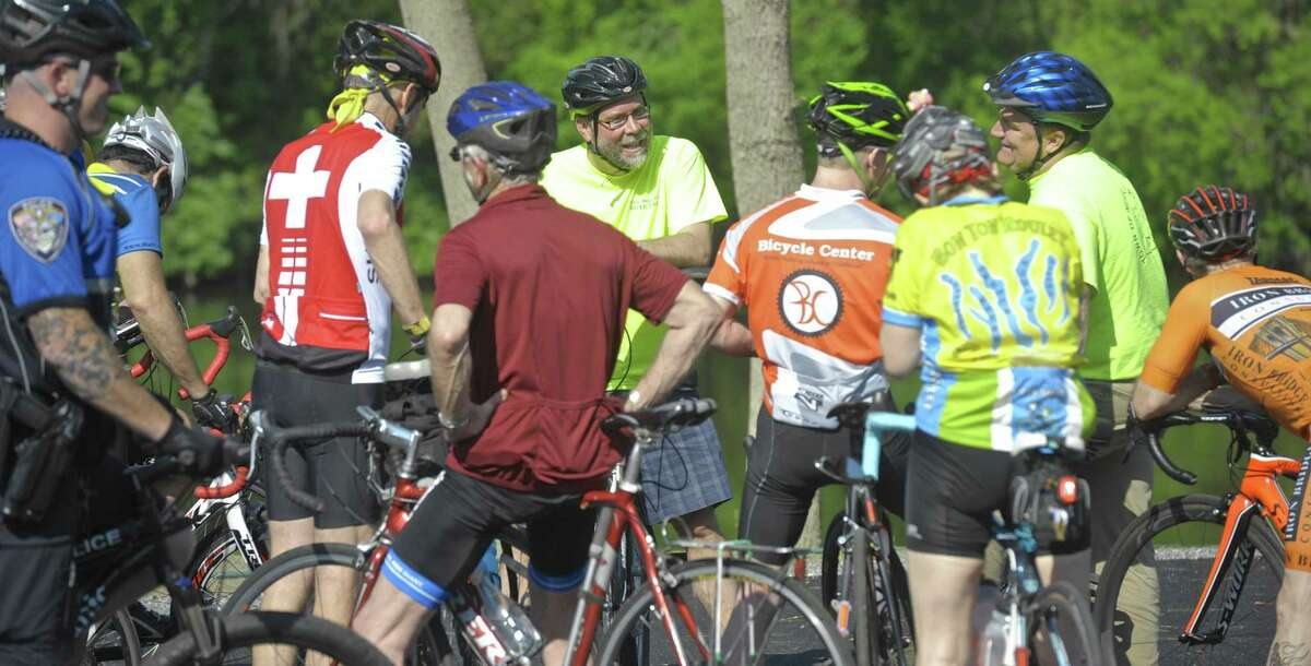 Cyclists stop at Young's Field Riverwalk to talk with Mayor David Gronbach, center, during New Milford's second annual Bike to Work event Friday.