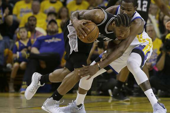 San Antonio Spurs forward Kawhi Leonard, left, dribbles against Golden State Warriors forward Kevin Durant during Game 1 of the NBA basketball Western Conference finals in Oakland, Calif., Sunday, May 14, 2017. (AP Photo/Jeff Chiu)