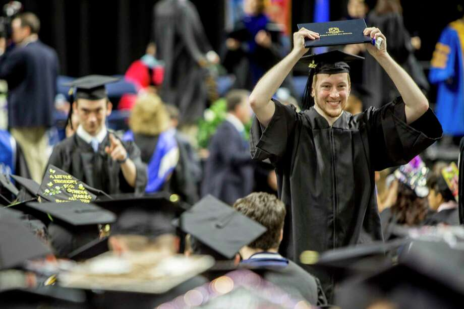 Vincent Baumann of Milford holds up his degree as he graduates with the Southern Connecticut State University class of 2017 at the Webster Bank Arena in Bridgeport, Conn. on Friday May 19, 2017. Photo: Johnathon Henninger, For Hearst Connecticut Media / Connecticut Post Freelance