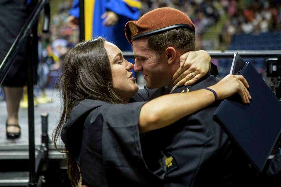 Deanna Bradley of Madison, hugs her fianceé, Harley Pretty, of Hamden just after he proposed after she accepted her Social Work Degree at Southern Connecticut State University at the Webster Bank Arena in Bridgeport, Conn. on friday May 19, 2017.  Pretty is  a member of the U.S. Army, a crew chief board Blackhawk helicopters. Photo: Johnathon Henninger, For Hearst Connecticut Media / Connecticut Post Freelance
