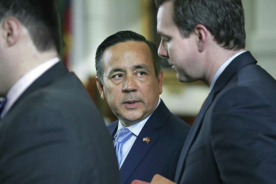 Sen. Carlos Uresti, who was indicted this week on various fraud, bribery and conspiracy allegations, gets some advice from his staff as he makes it back to the floor of the Senate chamber on May 17. The indictment came Tuesday and his arrest Wednesday. Photo: Tom Reel /San Antonio Express-News / 2017 SAN ANTONIO EXPRESS-NEWS