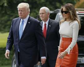 Vice President Mike Pence, center, watches as President Donald Trump and first lady Melania Trump walks across the South Lawn of the White House in Washington, Friday, May 19, 2017, before the president and first lady boarded Marine One for a short trip to Andrews Air Force Base, Md. Trump is leaving for his first foreign trip, visiting Saudi Arabia, Israel, Vatican, and a pair of summits in Brussels and Sicily. (AP Photo/Pablo Martinez Monsivais)