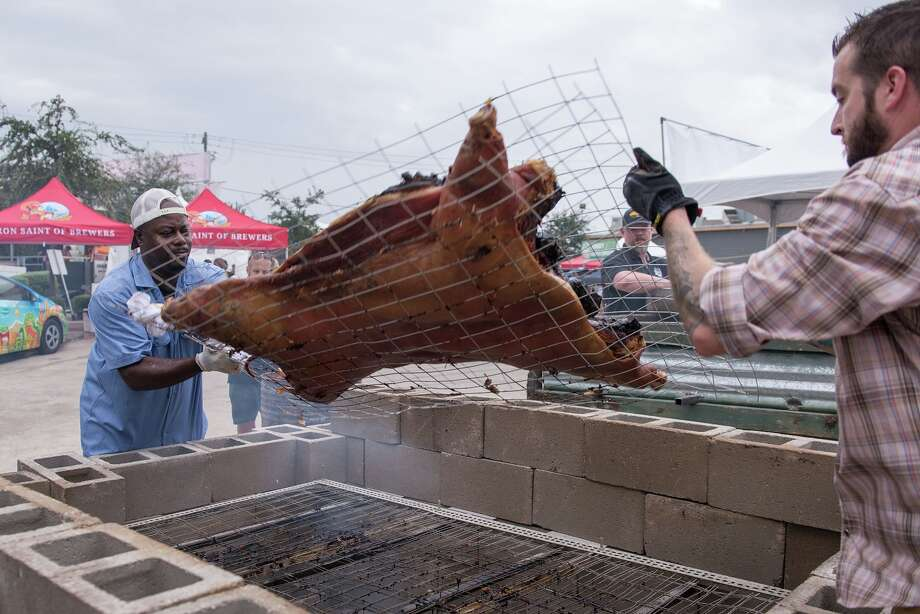 Rodney Scott and Patrick Feges flip a whole hog at Southern Smoke 2016. Photo: Catchlight Photography, Photographer / Owner / © 2016 Michelle Watson. All rights reserved.