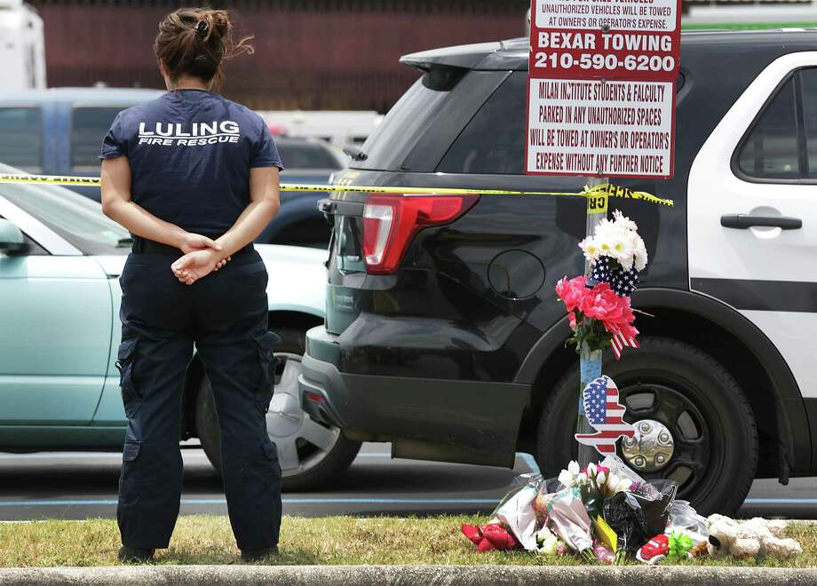 Pearl Pearson, a member of the Luling Fire Department, stands near a spread of flowers placed by passerbys, honoring San Antonio firefighter Scott Deem, who was killed during a blaze at the Northwest Side strip mall on Ingram Rd. Photo: Bob Owen, Staff / San Antonio Express-News / ©2017 San Antonio Express-News
