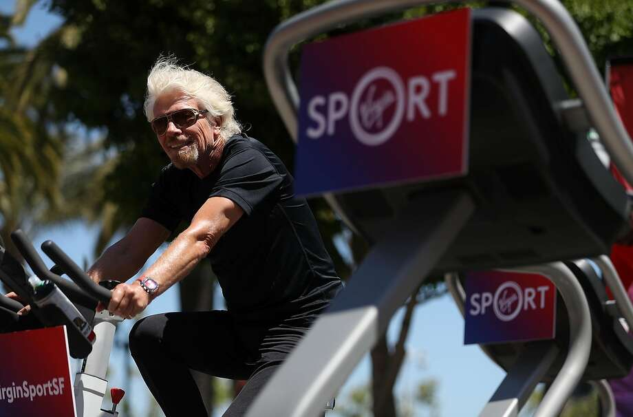 Sir Richard Branson rides an exercise bike in San Francisco in May as he announces the inaugural Virgin Sport festival. The event has been canceled because of poor air quality. Photo: Justin Sullivan, Getty Images