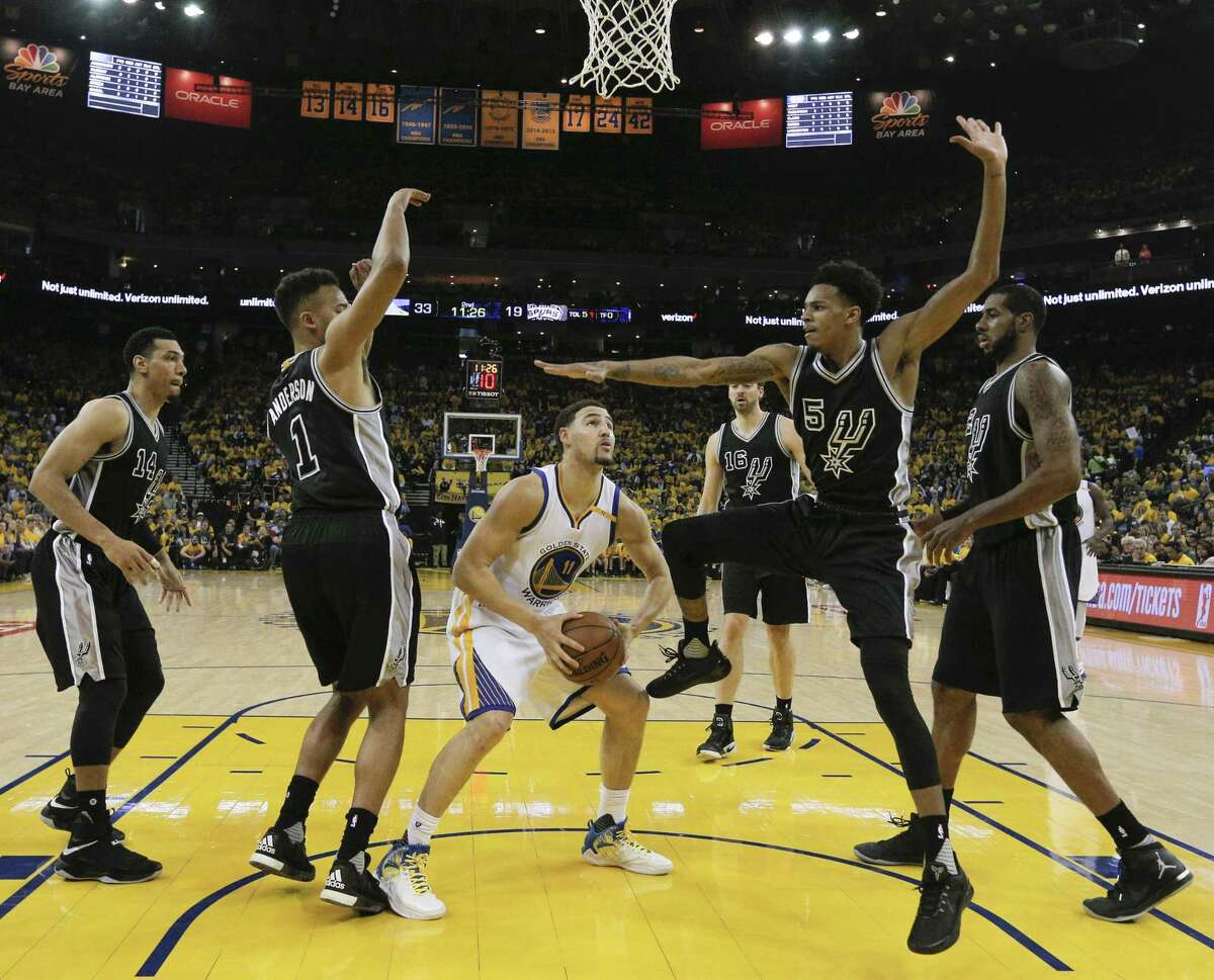 Golden State Warriors' Klay Thompson is surrounded by five Spurs during Game 2 of the Western Conference finals at Oracle Arena on May 16, 2017 in Oakland, Calif.