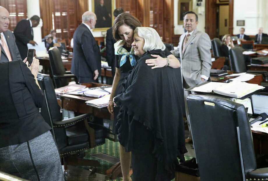 Senator Judith Zaffirini, D-Laredo, gets a hug from Senator Lois Kolkhorst, R-Brenham, after she wins passage in the Senate of her bill to ban texting while driving as legislators work at the Texas Capitol on May 19, 2017. Photo: Tom Reel, Staff / San Antonio Express-News / 2017 SAN ANTONIO EXPRESS-NEWS