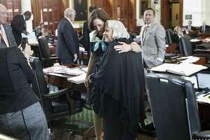 Senator Judith Zaffirini, D-Laredo, gets a hug from Senator Lois Kolkhorst, R-Brenham, after she wins passage in the Senate of her bill to ban texting while driving as legislators work at the Texas Capitol on May 19, 2017.